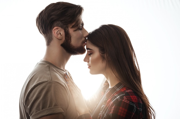 Tender picture of young couple. man kissing woman to forehead.