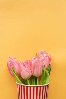 Tender pink tulips inside of red striped cup on pastel yellow background. flat lay. copy space. place for text. concept of international women's day, mother's day, easter. valentines love day