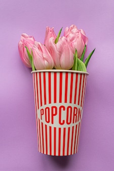 Tender pink tulips inside of red striped popcorn cup on pastel violet background. flat lay. copy space. place for text. concept of international women's day, mother's day, easter. valentines love day