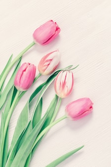 Tender pink tulips on white wooden table with copy space for your text or congratulations. greeting card for spring time concept. pastel colors. vertical format, view from above.
