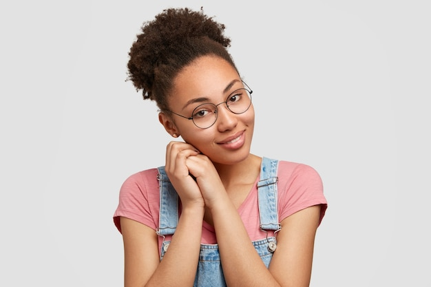 Tender pleased mixed race woman with charming smile, keeps hands near face, wears glasses tilts head, wears casual clothing, isolated over white  wall, happy to be invited on party with friends