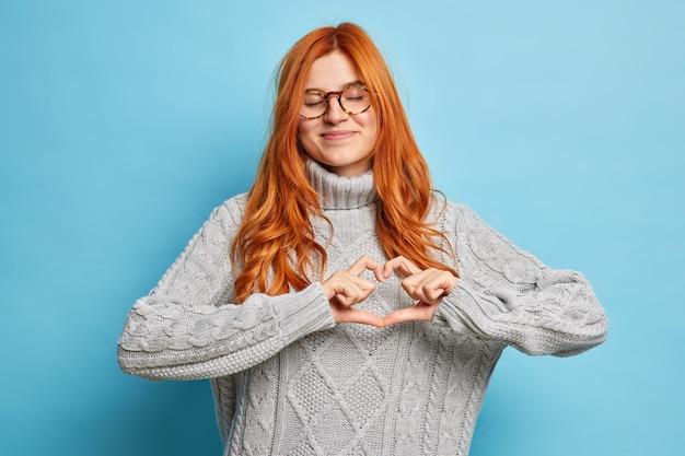 Tenera donna rossa soddisfatta fa il gesto del cuore esprime amore a qualcuno chiude gli occhi con piacere ha umore romantico indossa un maglione lavorato a maglia.