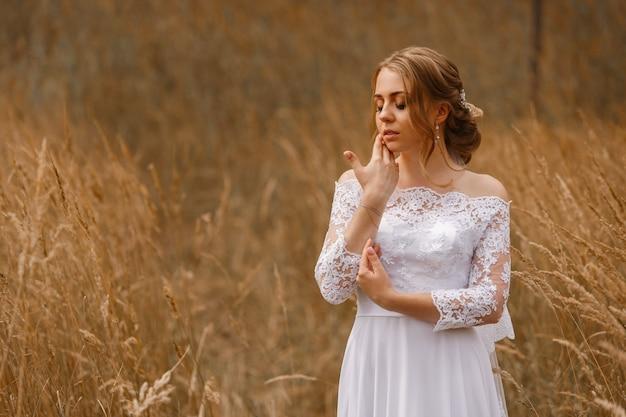 화창한 날 야외에서 베일과 하얀 드레스를 입고 신부의 부드러운 초상화. 성격에 결혼식입니다. 귀여운 여자의 얼굴을 닫습니다. 헤어 스타일을 가진 아름 다운 신부와 밀밭에서 메이크업