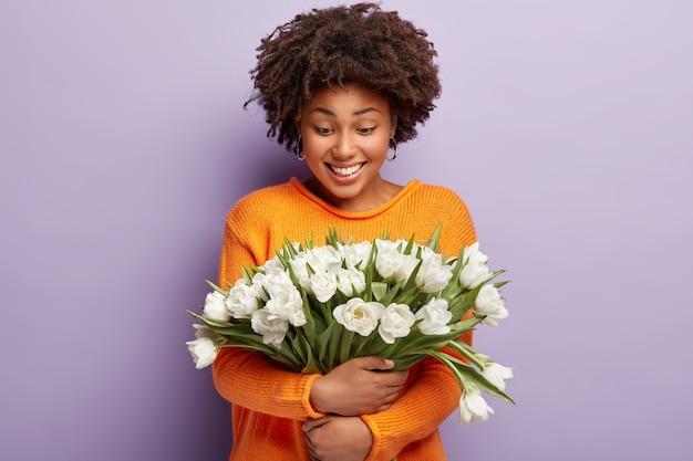 Нежная позитивная афроамериканка обнимает нежно белые цветы, нежно улыбается и смотрит на тюльпаны, носит оранжевый джемпер
