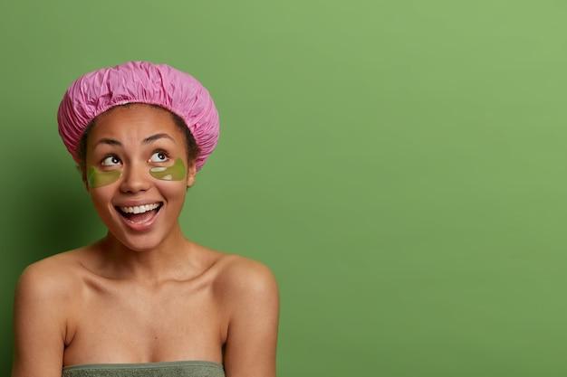 콜라겐 아이 패드를 가진 부드러운 긍정적 인 어두운 피부의 여성, 위에 집중, 긍정적으로 미소, 맨손으로 어깨, 목욕 모자 착용, 순수한 깨끗한 피부를 가졌습니다. 바디 케어 루틴. 녹색 벽