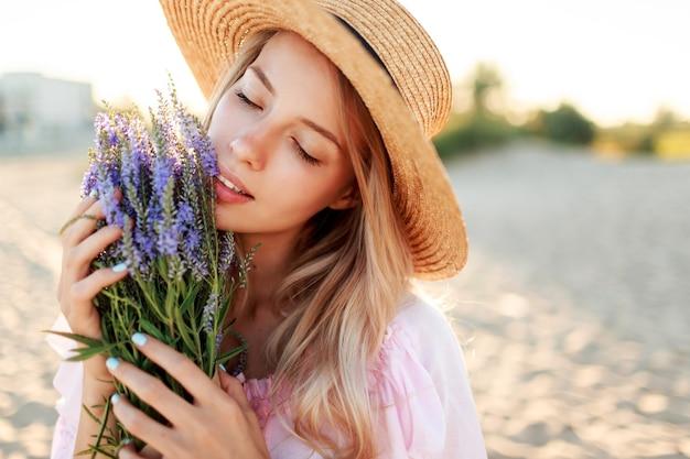 Tenera bella donna in cappello di paglia in posa sulla spiaggia soleggiata vicino all'oceano con bouquet di fiori. close up ritratto.