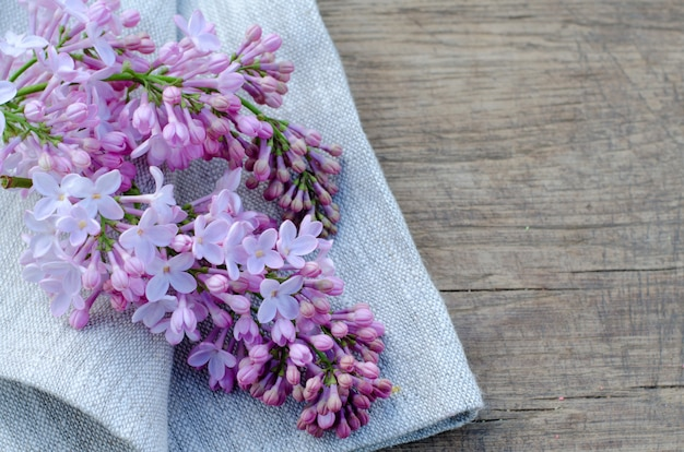 Tender purple lilac flowers on linen fabric