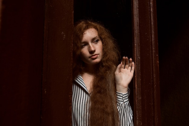 閉じたガラスのドアの後ろに立っている柔らかい赤い髪のモデル。ガラスの雨滴