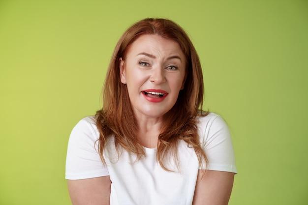 優しい赤毛元気な中年のお母さんがため息をつく幸せの誘惑笑顔喜んでいる表情魅惑の魅惑的なカメラをチェックしてくださいかわいい素敵なシーンが溶ける心温まる瞬間緑の壁