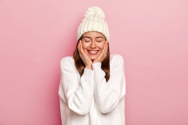 이빨 미소를 지닌 부드럽고 편안한 평온한 여성은 흰색 캐주얼 점퍼와 모자를 쓰고 즐겁고 괴롭지 않으며 눈을 감고 핑크색 배경에 포즈를 취합니다.