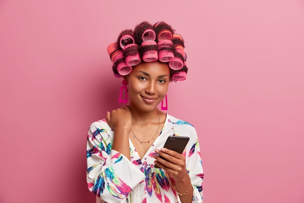 Tender retro housewife with hair rollers, beauty face, holds mobile phone, watches video, dressed in casual dressing gown, poses indoor.