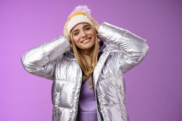 재미 보이는 겨울 스키 리조트 휴가를 즐기는 부드러운 낭만적 인 매력적인 금발 여성은 은색 세련된 재킷, 보라색 배경을 입고 모자를 만지고 광범위하게 기울어 진 머리를 웃고 기쁘게 생각합니다.