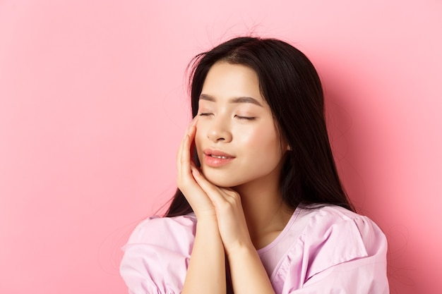 Tender and romantic girl gently touching face, close eyes and smiling softly, standing on pink background. concept of skincare.