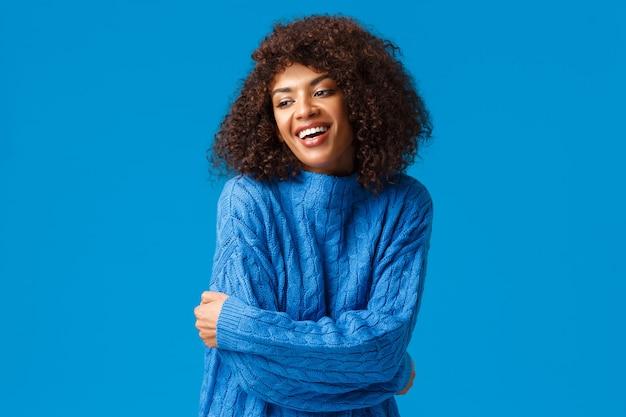 Ragazza afroamericana sorridente tenera, romantica e sensuale, che abbraccia il proprio corpo, concetto di auto-accaptence. guardando allegramente di traverso, abbracciandosi per riscaldarsi