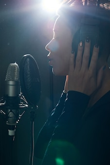 Tender singer in headphones recording music