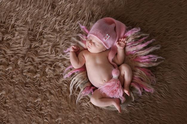 Tender sleeping newborn baby in pink cap