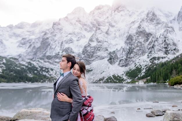 Нежная улыбающаяся пара в свадебном наряде стоит перед красивым зимним горным пейзажем