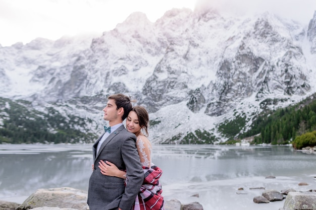 Tender smiled couple in wedding attire is standing in front of the beautiful winter mountain scenery