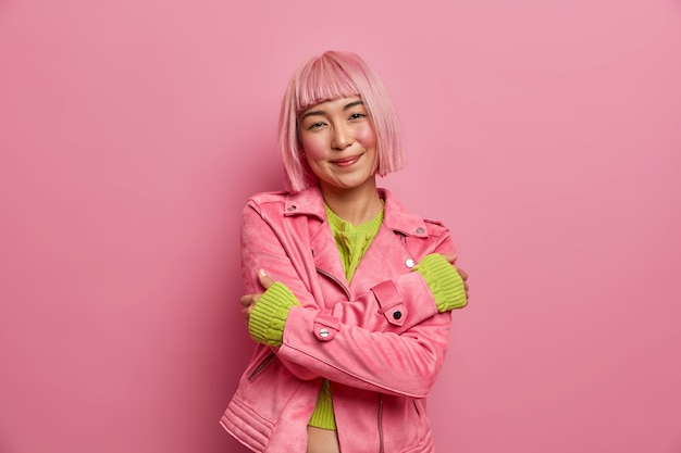 Tender smiling asian woman has dyed hairstyle loves herself, embraces body, dressed in casual jacket