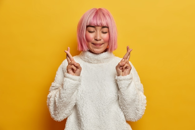 Tenera donna asiatica sorridente con i capelli rosei, chiude gli occhi e incrocia le dita per buona fortuna, esprime desideri, ha fede, vuole raggiungere il successo