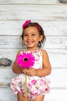 Tender smiling toddler, with a flower in her hand