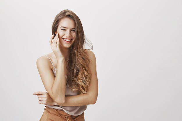 Tender smiling woman touching cheek and laughing