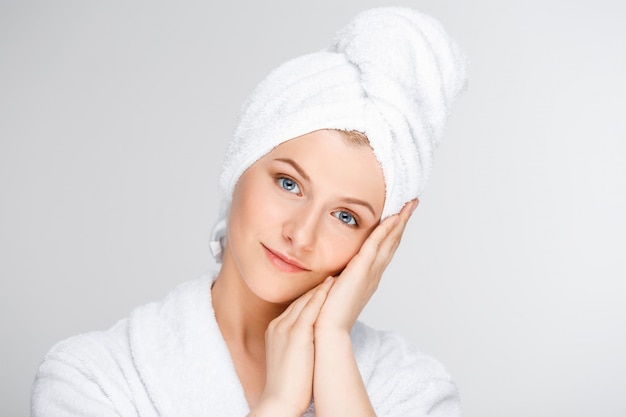 Tender smiling woman touching clean face
