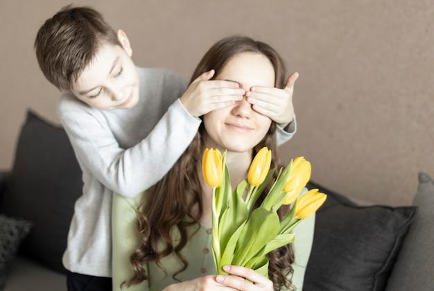 Нежный сын закрывает маме глаза, делая ей сюрприз, и дарит ей тюльпаны, поздравляя с днем матери во время празднования дома.