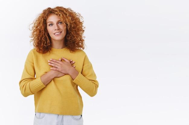 Нежная, трогательная рыжая кавказская женщина с кудрявыми рыжими волосами, прижала руки к сердцу и вздыхает с благодарной улыбкой, выглядит довольной и польщенной, когда получает романтический подарок, белая стена