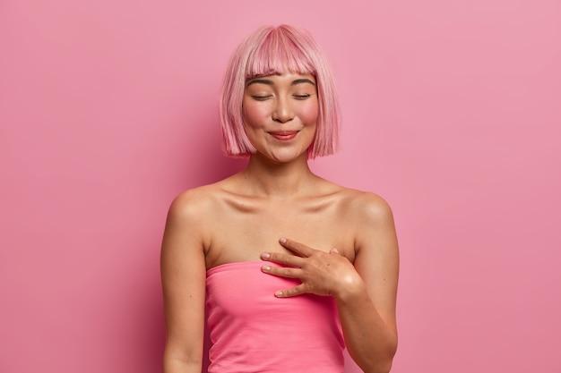 부드러운 만진 여자는 눈을 감고, 손을 가슴 가까이에 두며, 선물을 받고 기뻐하며, 사랑스러운 데이트를 회상하고, 분홍색 머리카락을 염색하고, 캐주얼 한 옷을 입고,