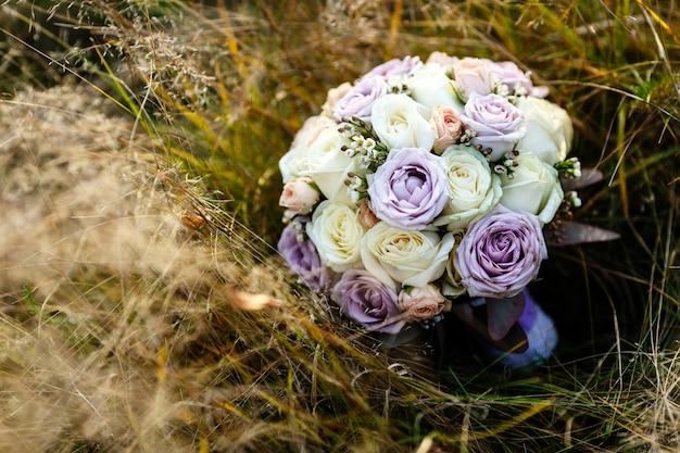 베이지 색과 보라색 장미로 만든 부드러운 웨딩 부케는 마른 잔디에 놓여 있습니다.