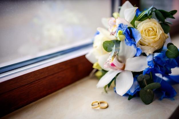Нежный свадебный букет из кремовых, слоновой кости и розовых роз на подоконнике