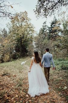 강아지와 함께 가을 숲에서 사랑에 부드러운 웨딩 커플이 걷고있다