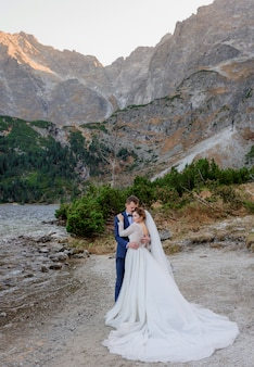 Tender wedding couple is standing on the picturesque landscape of autumn high mountains