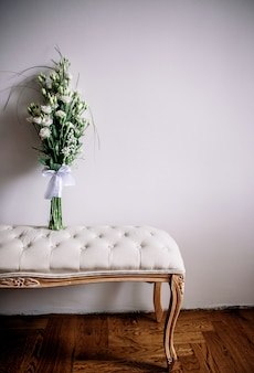 Tender white bouquet stands on a little sofa