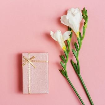優しい白い花のフリージアとピンクの閉じたギフトボックス