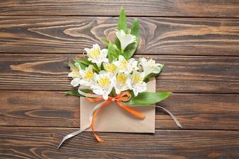 Нежные белые цветки маленьких орхидей в хитром почтовом конверте на деревянном фоне