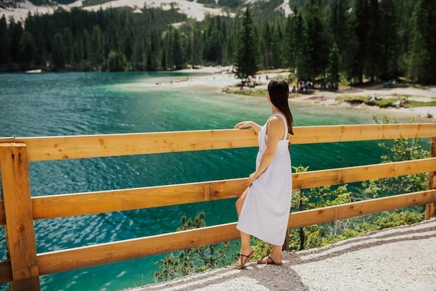Tender woman in beautiful white dress poses on lake braies