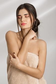절차 후 스파 치료 후 부드러운 피부를 즐기는 부드러운 여자.