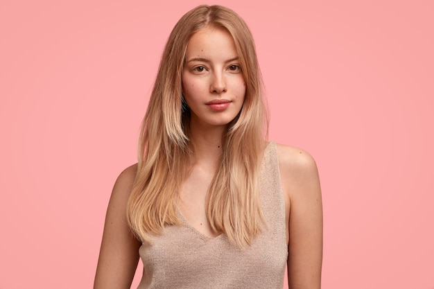Tender woman feels gentle and beautiful, wears casual beige t-shirt, has straight light hair, isolated over pink wall, looks seriously, demonstrates natural beauty, has no make up