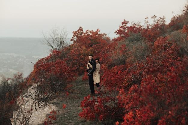 Нежная женщина в бежевом плаще обнимает своего стильного парня сзади