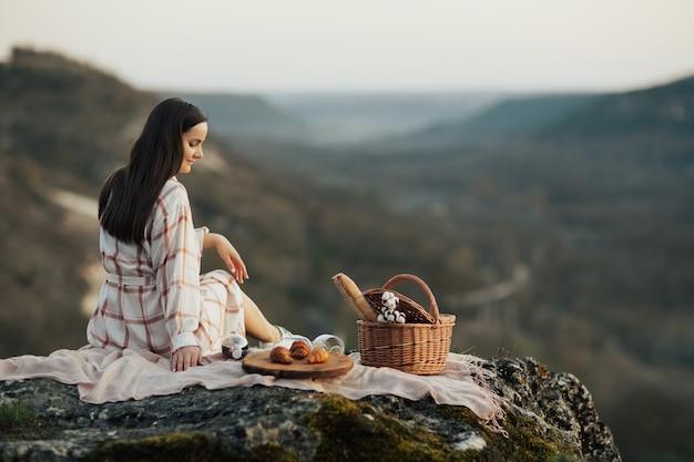 ピクニックだけで自然の中で休んでいるドレスを着た優しい女性