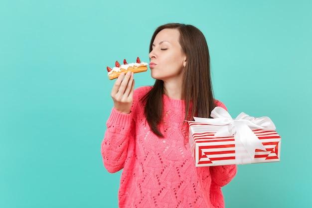 エクレアケーキ、青い背景で隔離のギフトリボンと赤いプレゼントボックスを保持している目を閉じてピンクのセーターの優しい女性。バレンタイン、女性の日、誕生日の休日のコンセプト。コピースペースをモックアップします。