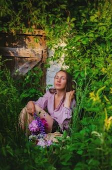 Нежная женщина отдыхает в травянистых зарослях с красивым букетом пионов и полевых цветов