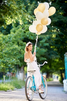 Tender woman on vintage bicycle with balloons looks with smile