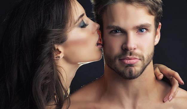 優しい若いカップルキスカップルの肖像画クローズアップ若いカップルのキス筋肉質の男を抱きしめてキスするセクシーな女性官能的なキス