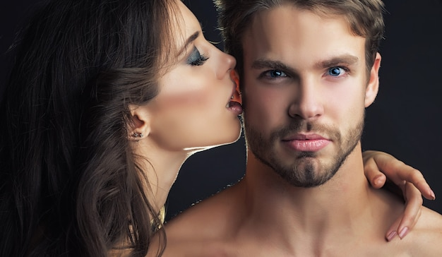 Tender young couple kissing couple portrait closeup young couple kiss sexy woman embracing and kissing muscular man sensual kisses