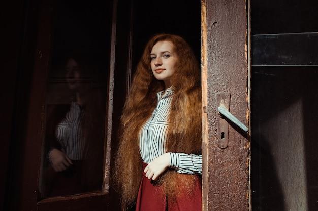 緑豊かな赤い髪とそばかすが古いドアに立っている優しい若い生姜モデル