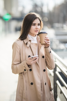 優しい若い女性が外の自分のカップからコーヒーを飲んでいます。