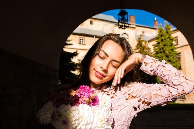 花の花束を保持している優しい若いモデル。彼女の顔に影とアーチでポーズをとる女性